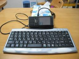 W-ZERO3 [es]を箱ティッシュにもたれかけさせ、USBキーボードを接続した時の様子(正面から見た時の様子)