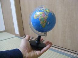 100円ショップ・シルクで購入した「No.8053 スタンド地球儀」(左手の上)